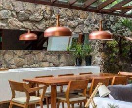 pendente cobre para varanda gourmet decorada com mesa de madeira e parede de pedra  Foto Liv Decora