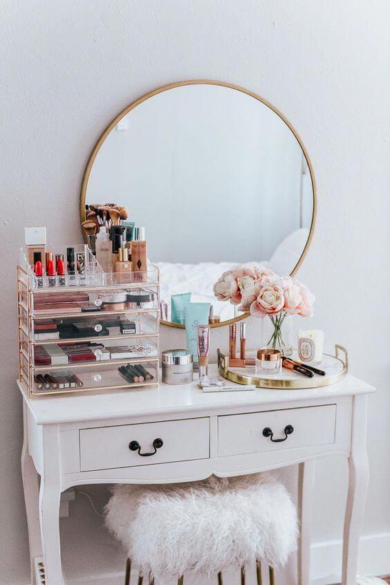 Penteadeira com maquiagens e gaveteiro no quarto