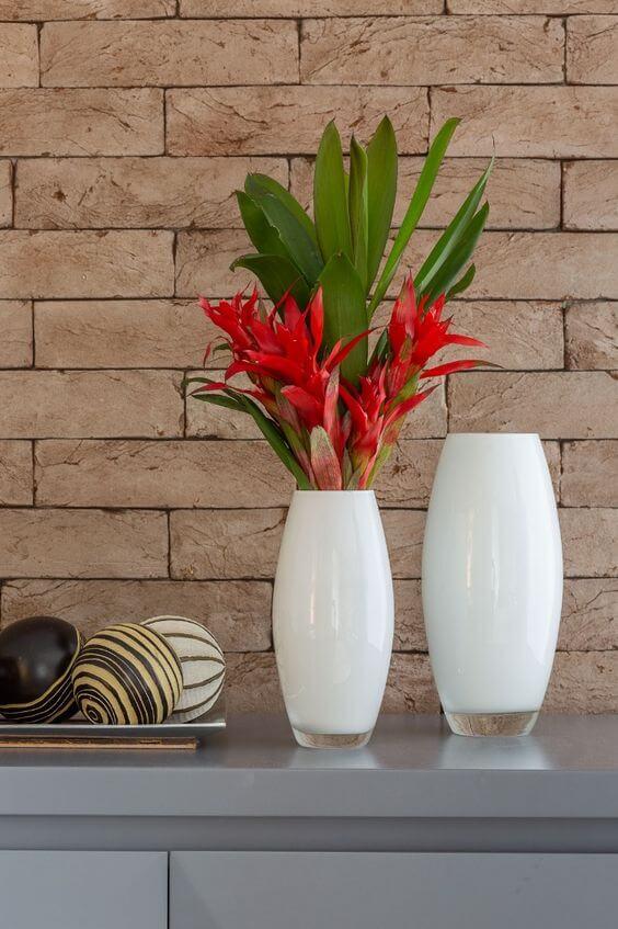 Plantas com flores vermelhas no vaso branco