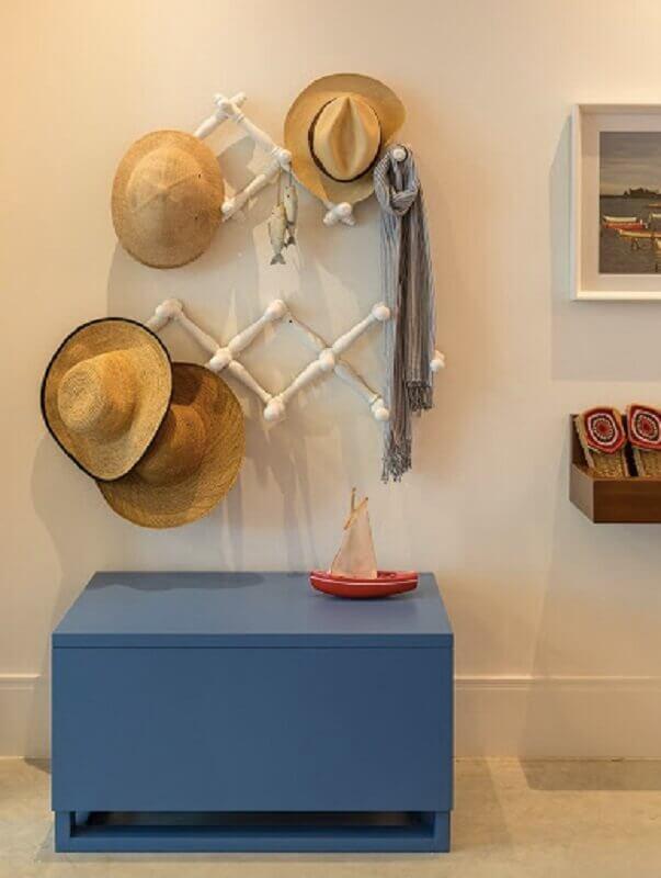 quarto de praia com cabideiro de parede e bau azul