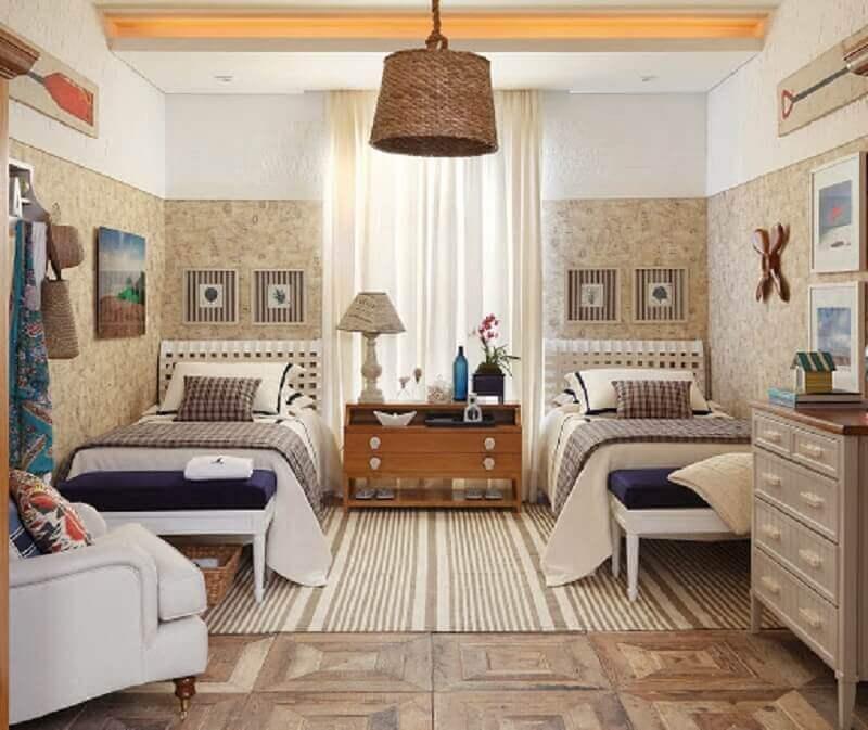 quarto de praia decorado em tons de bege com papel de parede e poltrona branca