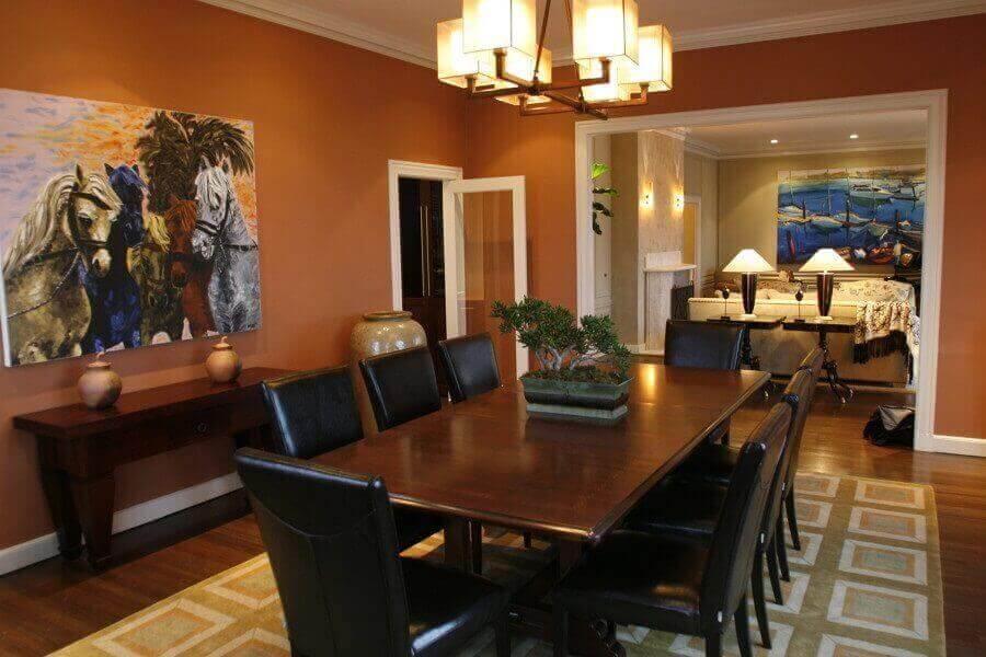 sala de jantar decorada com quadro de cavalos e cor de parede terracota Foto Pinterest