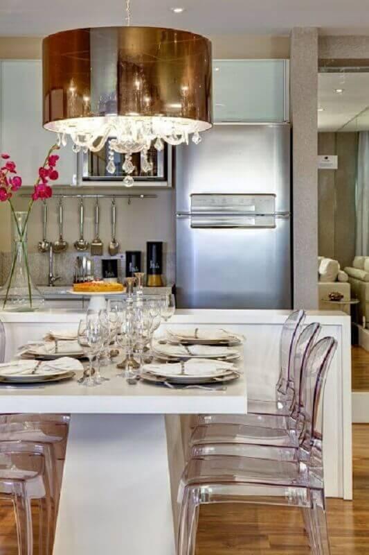 sala de jantar moderna toda branca com lustre pendente cobre e cadeiras de acrílico transparente Foto Otimizi