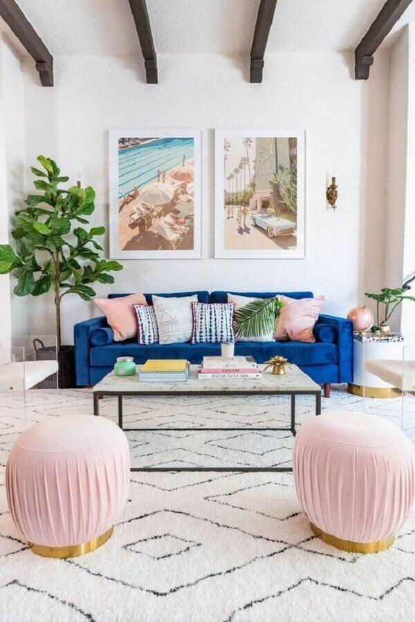 sala decorada com sofá azul de veludo e puff rosa redondo Foto Joss & Main