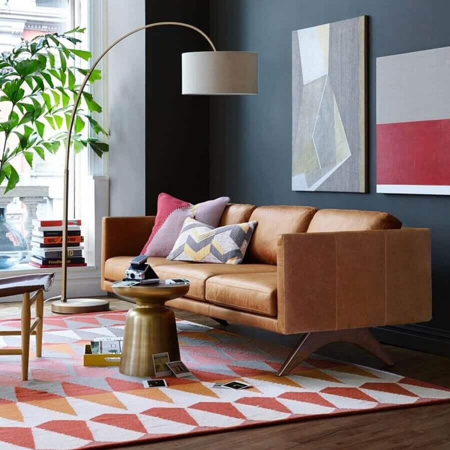 sala decorada com sofá de couro moderno e parede preta com quadros Foto Assetproject