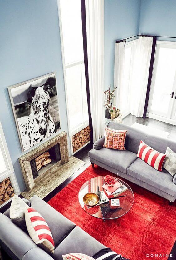Tapete vermelho para sala de estar com sofá cinza e parede azul