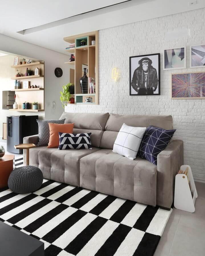 sofá cinza para decoração de sala com parede de tijolinho branca e tapete listrado preto e branco Foto Bianchi & Lima Arquitetura