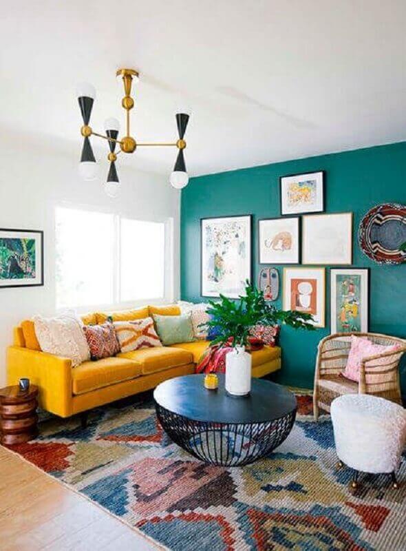 sofá com chaise amarelo para sala com tapete colorido e parede verde com vários quadros Foto Archilovers