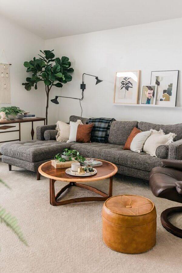sofá com chaise cinza para sala decorada com puff de couro e mesa de centro redonda de madeira Foto Article