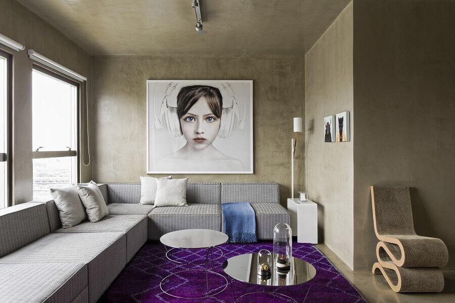 sofá de canto grande para sala moderna decorada com parede de cimento queimado e tapete roxo Foto Archello