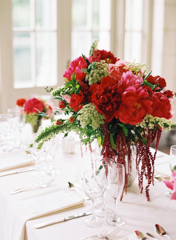 Arranjo de flores vermelhas decorando a mesa de jantar