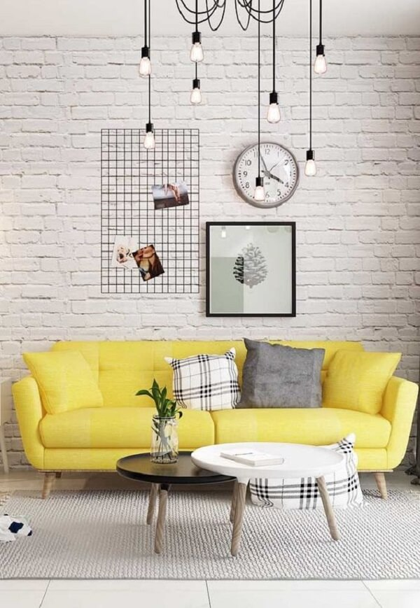 O sofá amarelo se destaca no ambiente com parede de tijolinho branco