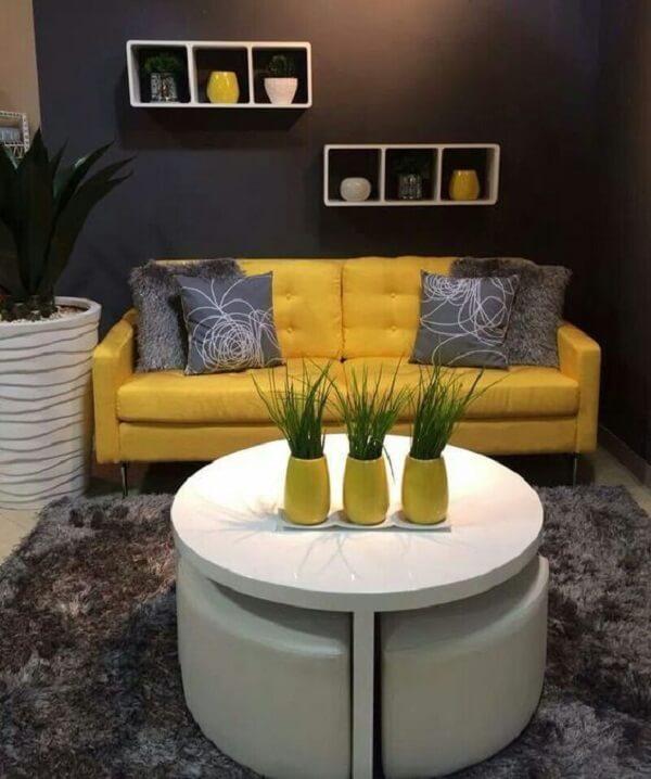 O sofá amarelo se harmoniza perfeitamente com os demais objetos decorativos do ambiente