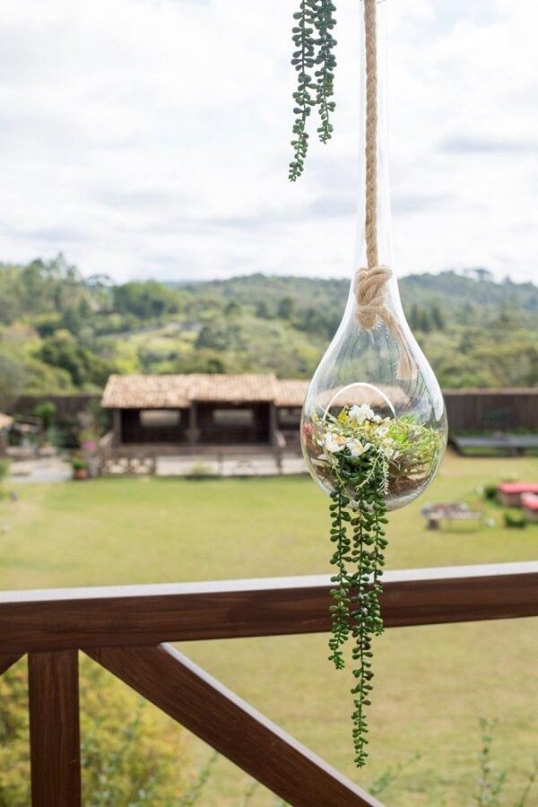 O cachepot de vidro suspenso decora a varanda da casa