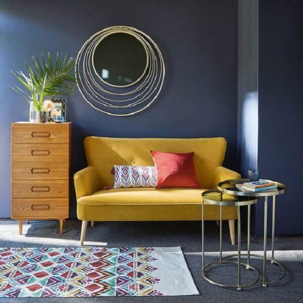 O sofá amarelo trouxe luminosidade para o cômodo com parede escura