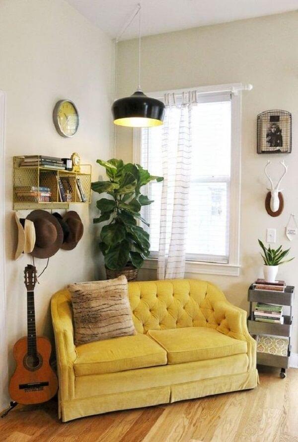 Sala de estar com pendente preto e sofá amarelo dois lugares