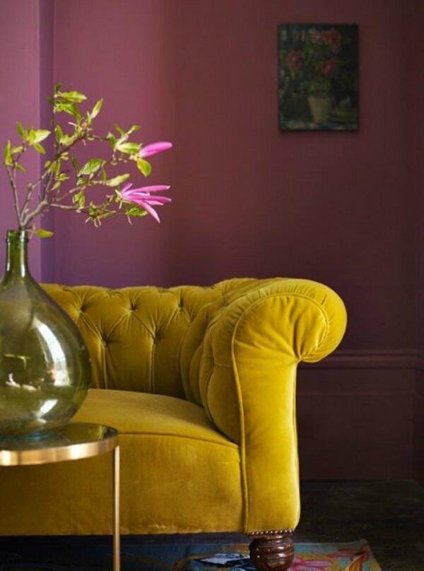 O sofá amarelo de veludo é o móvel de destaque desse cômodo