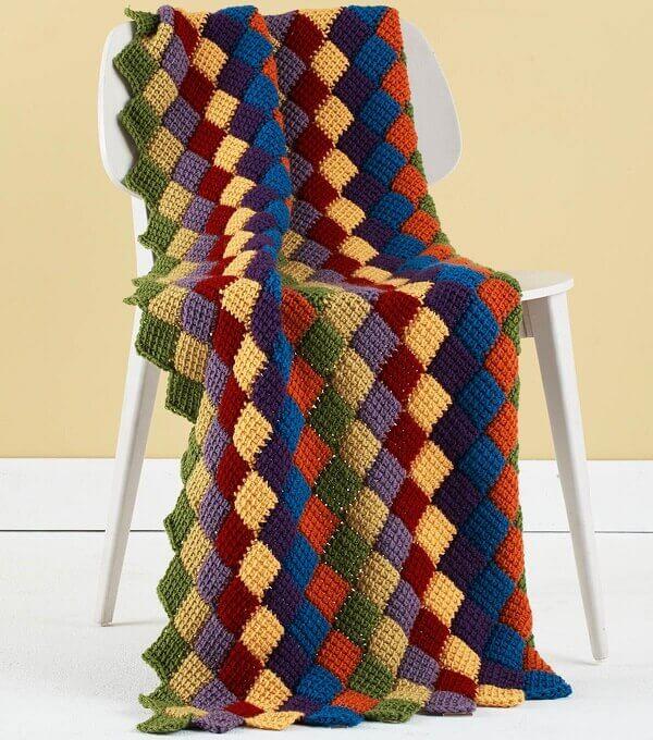 A manta colorida feita em crochê tunisiano traz descontração ao espaço