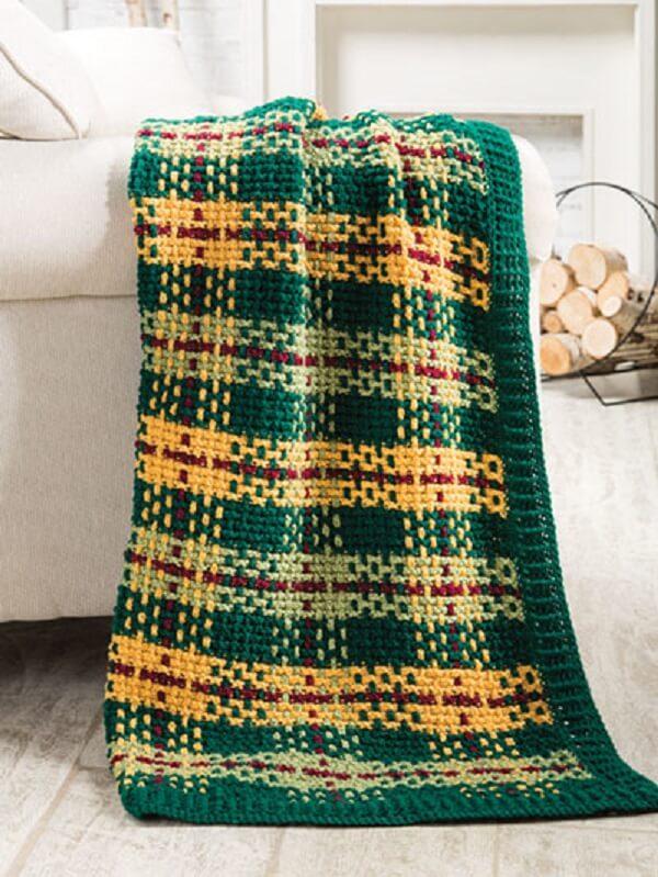 A manta feita em crochê tunisiano decora a sala de estar