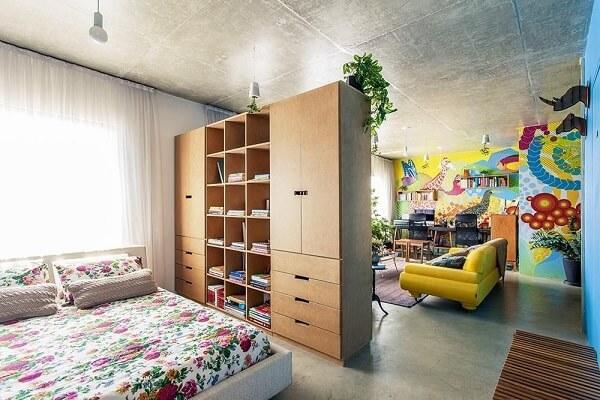 Armário de madeira, parede com pintura colorida e sofá amarelo