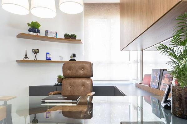Escritório planejado com cadeira de couro marrom e bancada de vidro comum