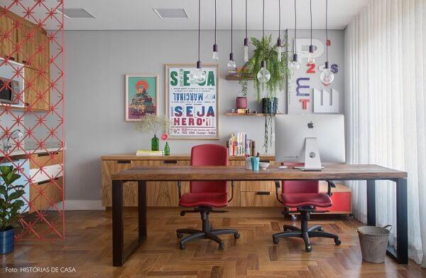 Escritório com mesa de madeira e luminária criativa