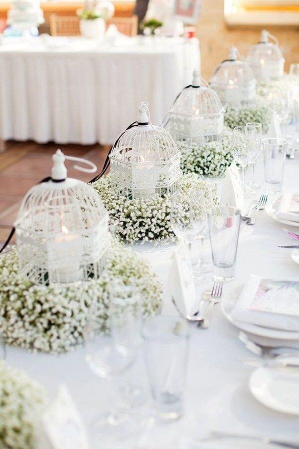 Gaiolas decorativas com flor mosquitinho e velas para a decoração de casamento