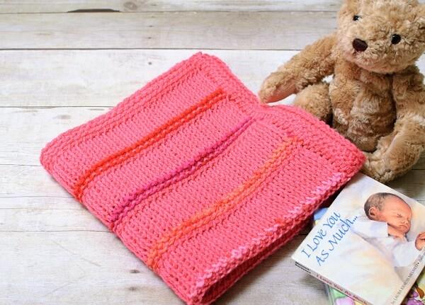 Manta de bebê em tom rosa feito em diferentes tipos de pontos de crochê tunisiano