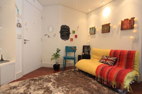 Quadros decorativos e sofá cama amarelo
