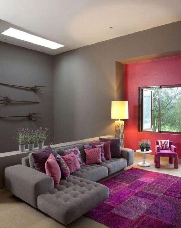 ala de estar com sofá cinza e tapete estampado em tons de rosa e roxo
