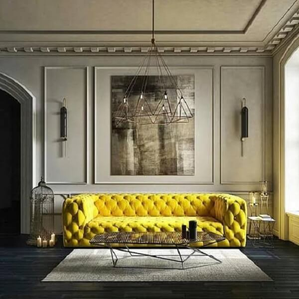 Sofá amarelo chesterfield e tapete cinza