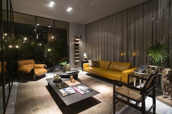 Sala de estar com poltrona mole e sofá amarelo de couro