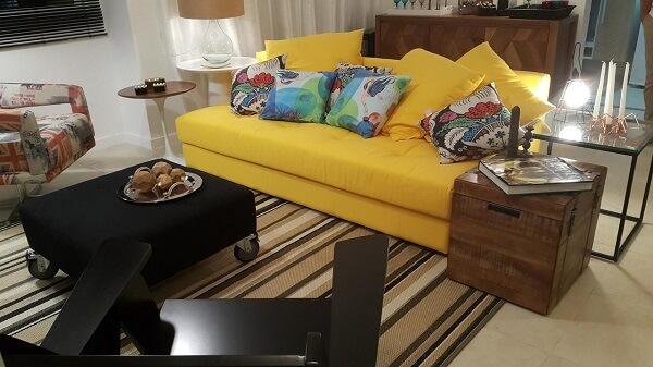 Sala com sofá amarelo e tapete listrado