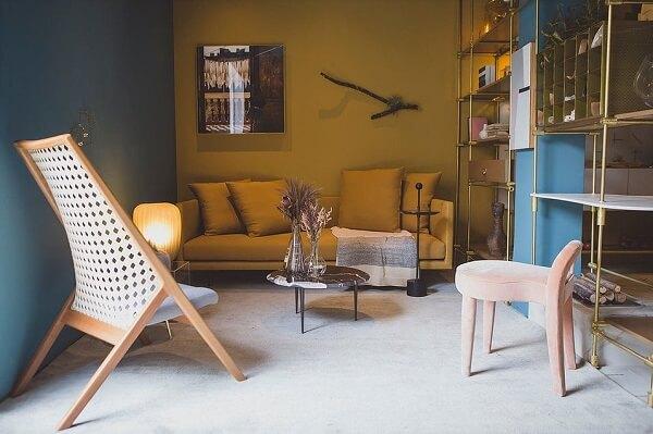 Sofá com tecido amarelo e estante metálica dourada