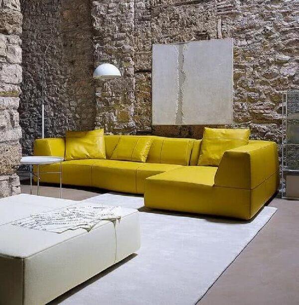 Sala de estar com parede de pedra e sofá de canto amarelo