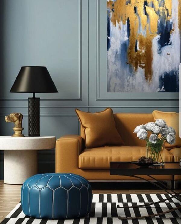 O sofá amarelo se harmoniza com o quadro abstrato da parede
