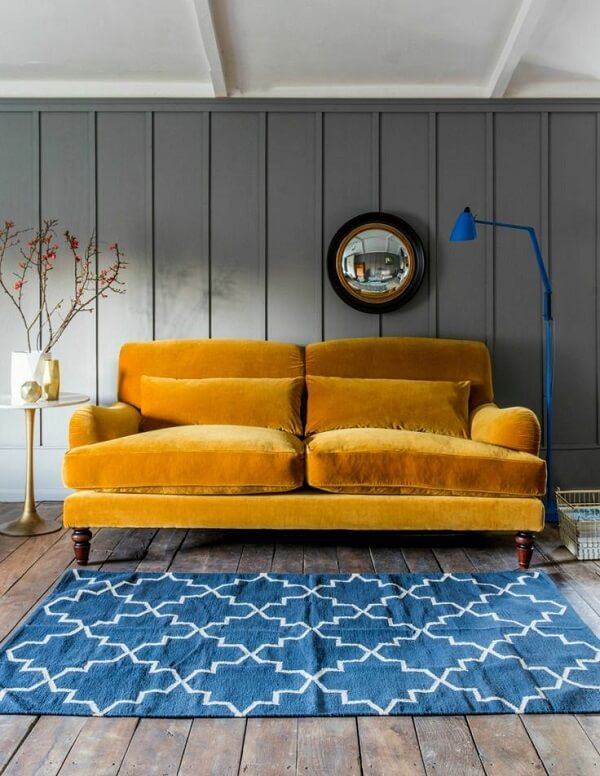 Sofá amarelo e luminária de chão azul