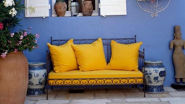 As almofadas lisas seguem a mesma tonalidade do assento do sofá amarelo