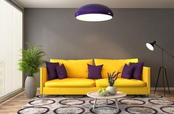 Sala de estar com sofá amarelo e almofadas roxas