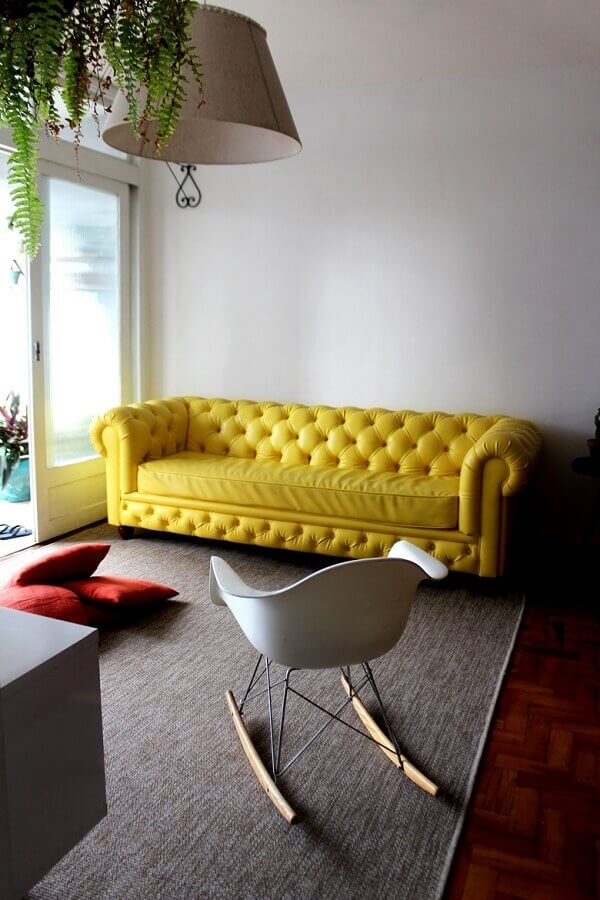 Sala de estar com sofá amarelo chesterfield e cadeira de balanço Eames branca