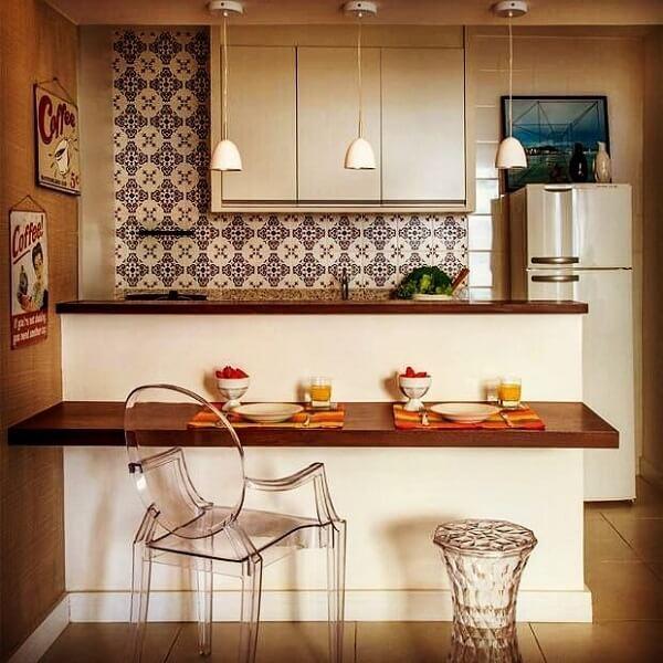 A bancada suspensa dessa cozinha é uma extensão mais baixa de mesa, utilizada para as refeições