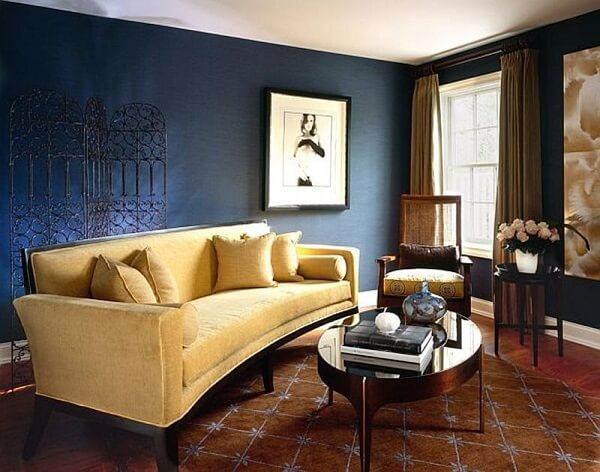 O sofá amarelo ilumina a sala de estar com paredes escuras