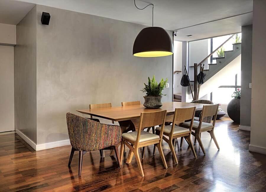 cadeiras estofadas para sala de jantar ampla decorada com parede de cimento queimado e pendente grande preto Foto Studio Scatena Arquitetura