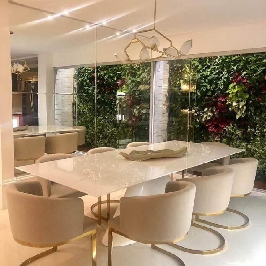 cadeiras estofadas para sala de jantar sofisticada decorada com jardim vertical e parede espelhada Foto Dicas Decor