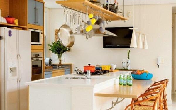 Cozinha americana com bancada suspensa de madeira