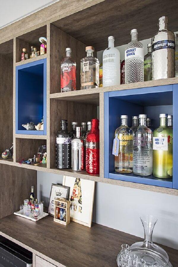 Os nichos coloridos foram utilizados para organizar as bebidas da casa