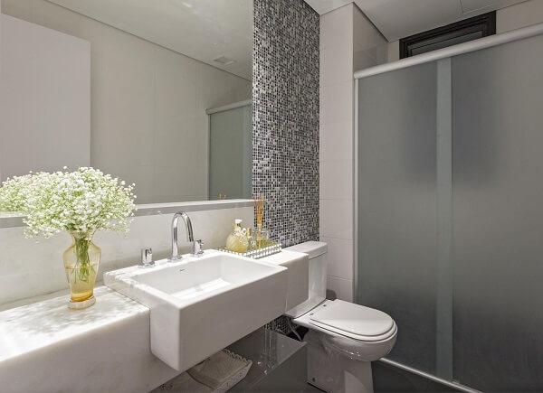 O recipiente de vidro com flor mosquitinho decora o banheiro