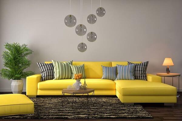 Modelo de sofá amarelo com chaise e almofadas listradas