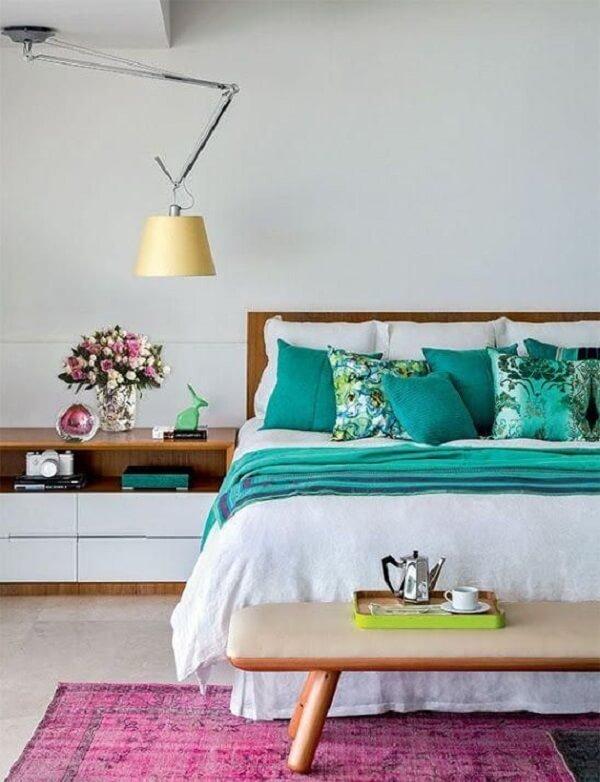 O tapete rosa no quarto pode ficar em parte debaixo da cama