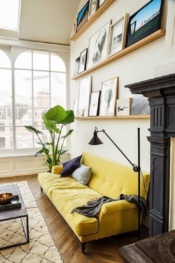 Sala de estar com sofá amarelo e prateleiras para quadros
